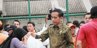 Diantara tumpukan sembako seorang warga sungkem pada Jokowi di Kelurahan Menteng Dalam, Tebet,