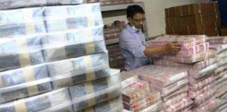 Petugas menata tumpukan uang rupiah.