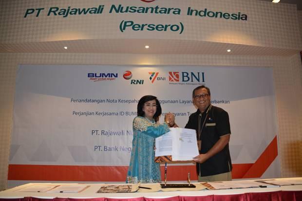 Dirut RNI Didik Prasetyo (kanan) bersama Direktur Hubungan Kelembagaan dan Transaksional Perbankan BNI Adi Sulistyowatisaat memperlihatkan replika dari Kartu ID karyawan RNI yang nantinya akan memiliki banyak fungsi antara lain sebagai uang elektronik.