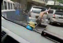 seorang pria yang diduga mengalami gangguan jiwa terlihat melakukan aksi heroik menolong ambulans yang terjebak di tengah lalu lintas yang padat.