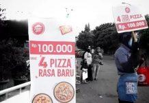 PegawaiPizza Hut menjajakan jualannya di pinggir jalan.